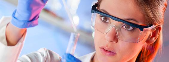 ricercatrice con occhiali di protezione che riempie una provetta con una pipetta